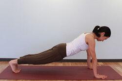5.呼吸を止めて、もう一方の脚を後ろへ引き、両手と足の爪先で体重を支える。頭と胴を一直線に保ち(腕立て伏せの体勢)、両手の間の床一点を見る。